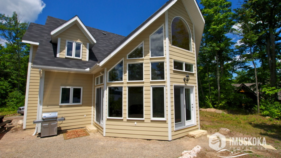 Beautiful Cottage level lot surrounding cottage, steps down to lake side and dock.