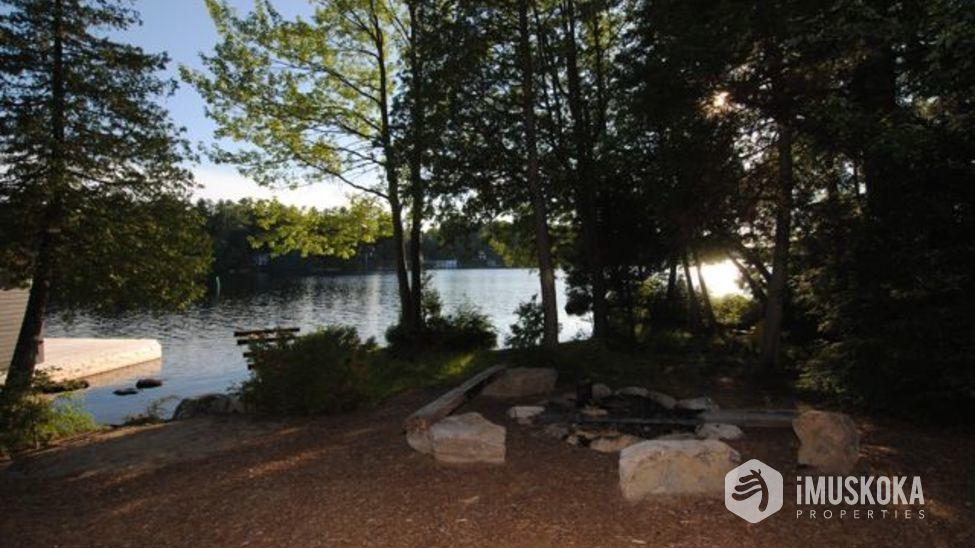 Level lands Level lot with fire pit at side of Lake Muskoka.